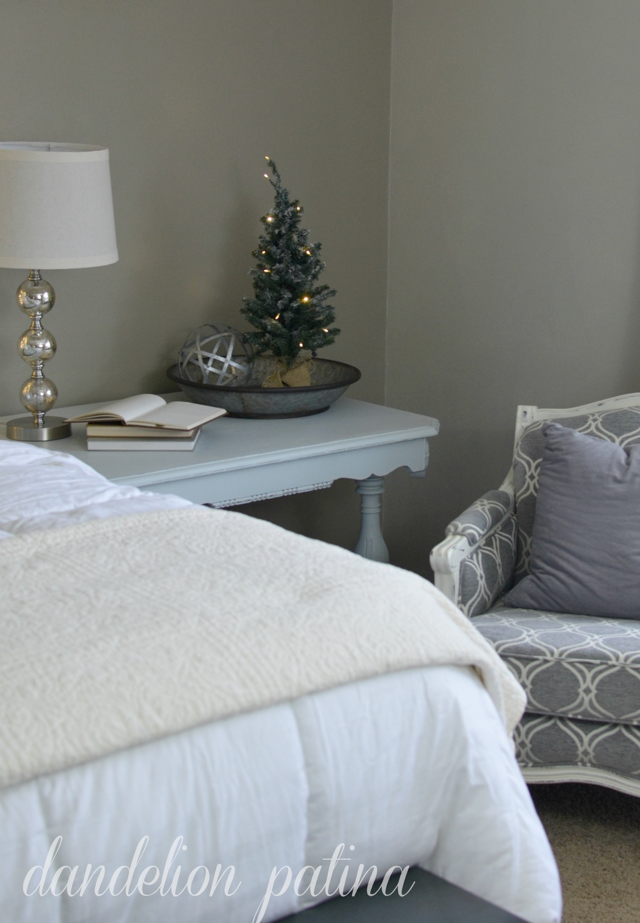 master bedroom with gray french chair