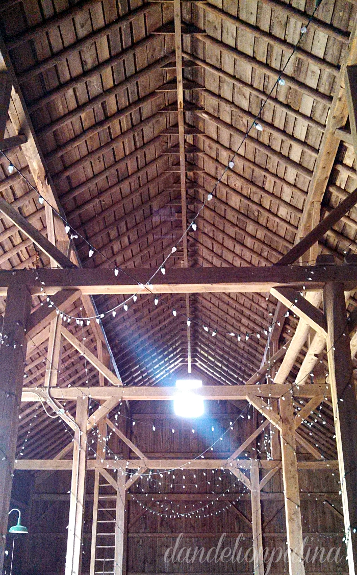 old barn interior with chunky wood beams and wood floors