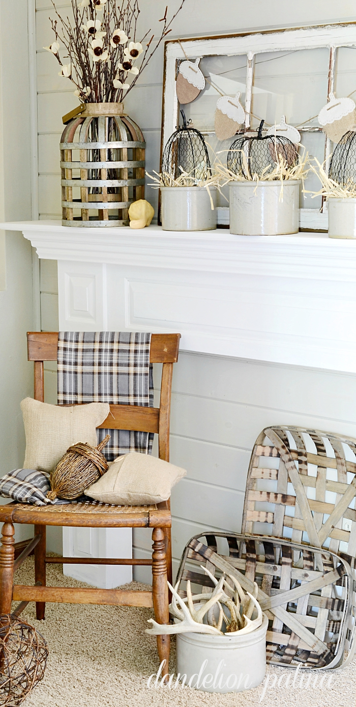 Neutral fall mantel incorporating farmhouse style with vintage wooden chair, tobacco baskets, and burlap pillows. Styling by dandelionpatina.com