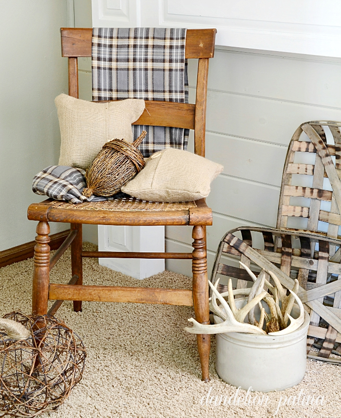 Neutral fall mantel with gray and tan plaid. Burlap pillows, deer antlers and tobacco baskets add farmhouse flair. Styling by dandelionpatina.com #farmhousestyle #fallmantel
