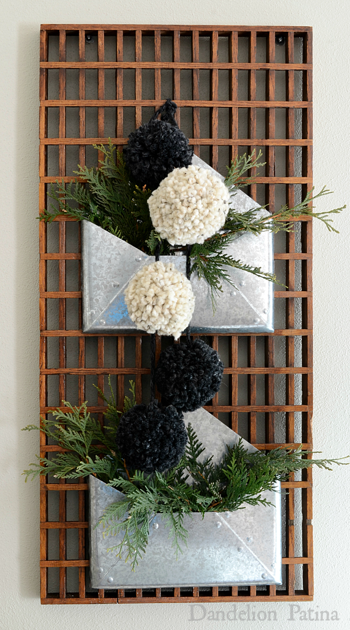 Happy Holidays Home Tour vintage wooden floor grate becomes wall art with galvanized envelopes, DIY pom pom garland, and sprigs of cedar via dandelionpatina.com