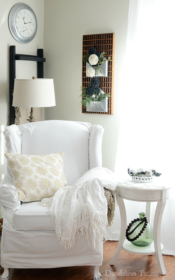 White slipcovered chair with neutral decor with a cottage style aesthetic via dandelionpatina.com