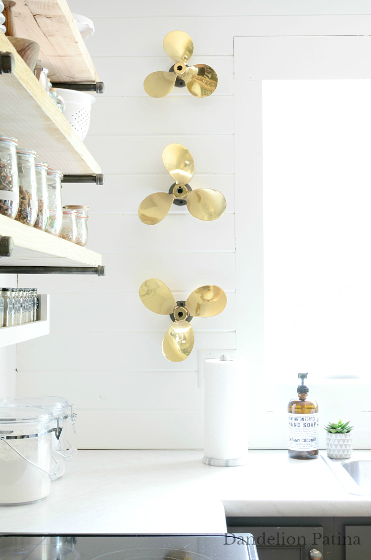 modern farmhouse kitchen white shiplap walls and vintage brass propellors for wall art